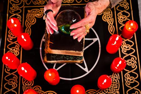 esot�risme: Femme diseuse de bonne aventure �sot�rique ou Oracle, voit dans l'avenir en regardant dans leur boule de cristal lors d'une S�ance de les interpr�ter et de r�pondre aux questions Banque d'images