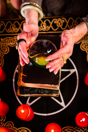 oracle: Female Fortuneteller or esoteric Oracle, sees in the future by looking into their crystal ball during a Seance to interpret them and to answer questions Stock Photo