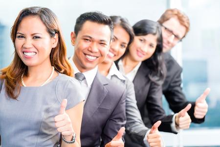 business asia: Ritratto della squadra asiatica di affari che mostra i pollici in su