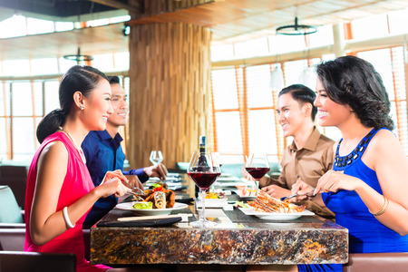 out to lunch: Asian Friends eating and drinking wine in restaurant