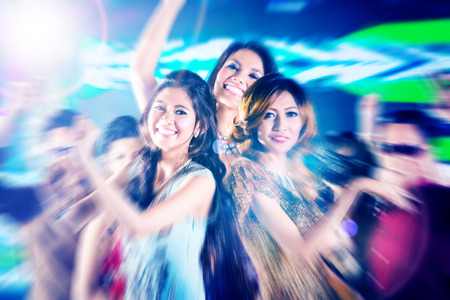 Asian beautiful friends dancing on disco floor having fun at fancy night club photo