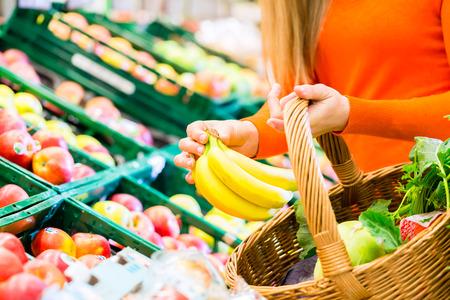 Kobieta w supermarkecie na zakupy dla owoców przydatności artykułów spożywczych, ona kładzie banana w swoim koszyku