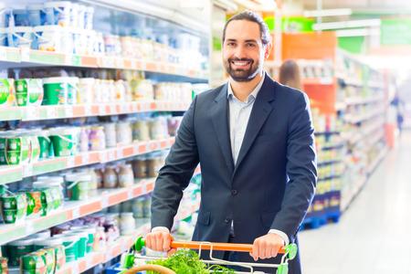 carretilla de mano: cliente con la carretilla de mano en el supermercado en busca de comestibles Foto de archivo