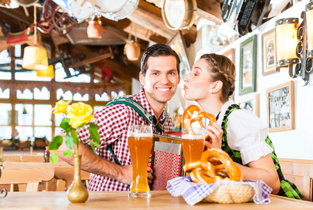 Bavarian man playing folk music for woman wearing dirndl photo