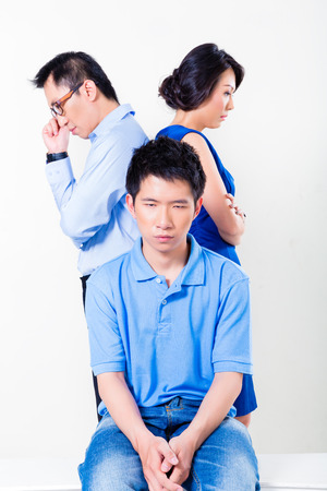 strife: Young Chinese boy suffering from fighting parents and their divorce, the argument is affecting the whole family Stock Photo