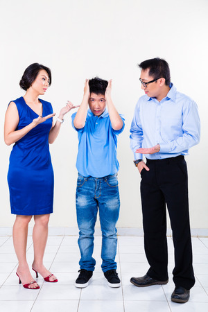 affecting: Young Chinese boy suffering from fighting parents and their divorce, the argument is affecting the whole family Stock Photo