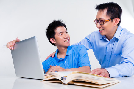 Chinese father helps his son with knowledge and experience for his complex and complicated homework assignments for the next day at school photo