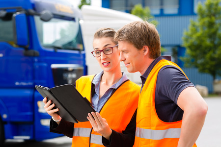 chofer: Log�stica - conductor orgulloso o transitario y compa�era de trabajo con la computadora tablet, en frente de los camiones y remolques, en un punto de transbordo, es un equipo bueno y exitoso