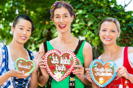Young women in traditional Bavarian clothes or tracht with a gingerbread souvenir heart in beergarden on Oktoberfest photo