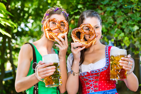 tracht: In Beer garden - female friends in Tracht, and Dirndl drinking a fresh beer and eating pretzel in Bavaria, Germany