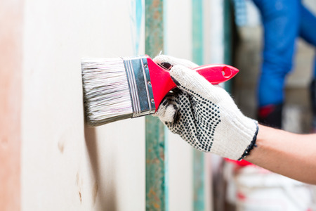 painter painting with a brush, color and protection gloves a wall of a tower building or construction site Stock Photo