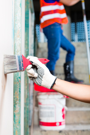 walling: painter painting with a brush, color and protection gloves a wall of a tower building or construction site Stock Photo
