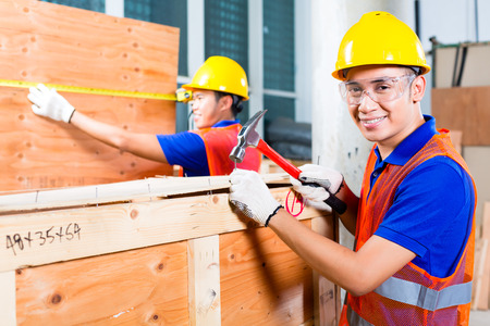 Asian Indonesian worker or craftsman and supervisor closing a delivery or wood box of a tower building or construction site with hammer and nail wearing a hardhat and protection glasses photo