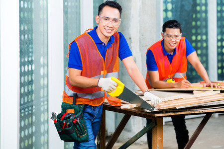sawing: Asian Indonesian builder or craftsman sawing with a saw a wood board of a tower building or construction site wearing protection glasses and gloves
