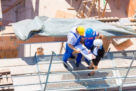 건설 현장의 팀 또는 설계자와 헬멧 작성기 또는 작업자가 발판 건설 계획 또는 청사진 또는 체크리스트에 대해 논의