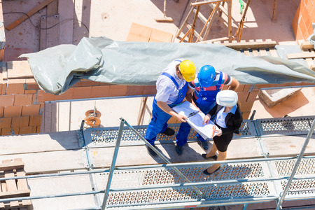 tallyman: Construction site Team or architect and builder or worker with helmets discuss on a scaffold construction plan or blueprint or checklist