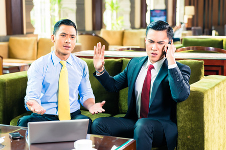 Asian Businessman talking on cell phone while having a meeting photo
