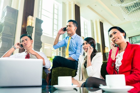 asian business team: Asian Businesspeople talking on cell phone Stock Photo