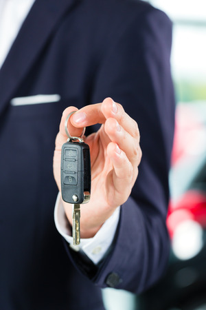 Seller or car salesman in car dealership with key presenting his new and used cars in the showroom photo