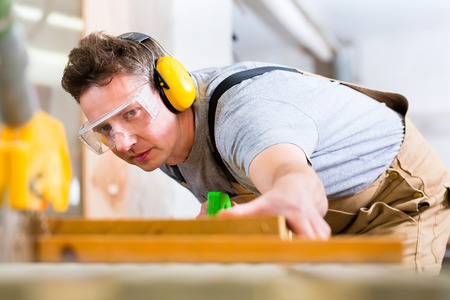 Carpenter arbeitet an einer elektrischen Kreissäge schneiden einige Bretter, er trägt Schutzbrille und Gehörschutz für die Sicherheit am Arbeitsplatz Standard-Bild
