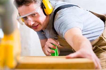 Carpenter werken aan een elektrische cirkelzaag te snijden boards, is hij het dragen van een veiligheidsbril en gehoorbescherming voor de veiligheid op de werkplek Stockfoto