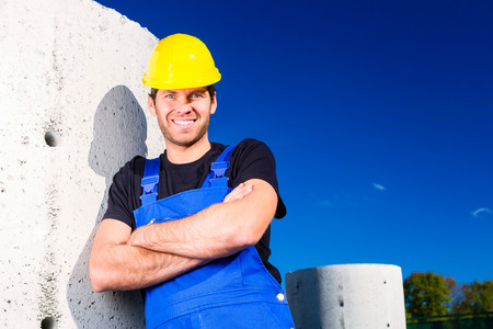 Pride builder standing on construction or building site with sewage or canalization concrete elements photo