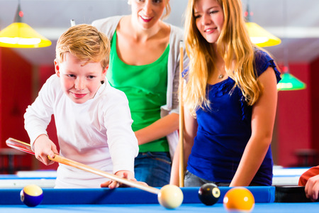 kick off: Family playing together billiard, Brother kick off with queue and balls on pool table
