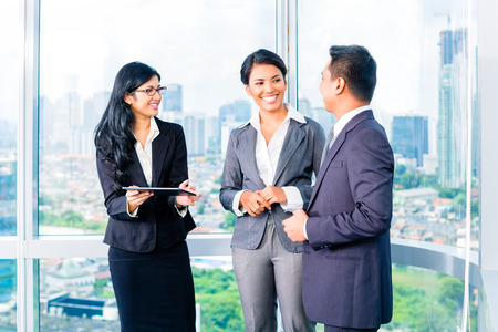 Asian Businesspeople standing in modern office photo