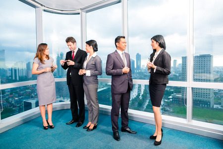 businessman standing: Asian Businesspeople standing and talking in front of office window Stock Photo