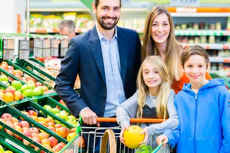 stores: Familie in supermarkt vruchten selecteert terwijl boodschappendienst