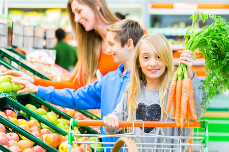 Family selecting fruits and vegetables while grocery shopping in supermarket  photo