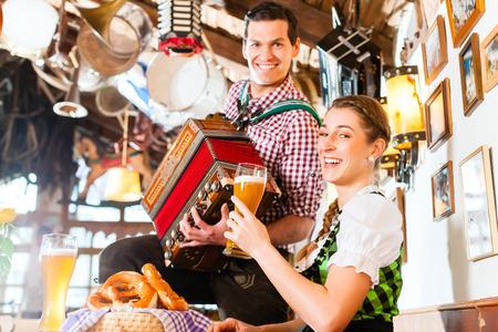 バイエルン人のギャザー スカートを着ている女性のための民俗音楽を演奏 写真素材 - 27413298