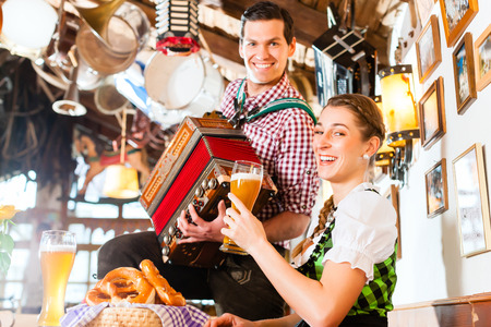 Bavarian man playing folk music for woman wearing dirndl