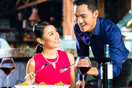 Portrait of Asian couple eating in restaurant Imagens - 27413311