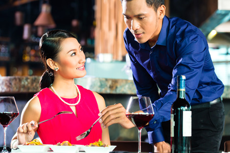 Portrait of Asian couple eating in restaurant photo