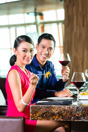 Portrait of happy Asian couple eating in restaurant