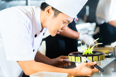 asian chef: Side view of young chef decorating cake Stock Photo