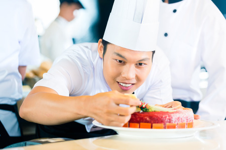 preparing food: Portrait of Asian chef decorating cake