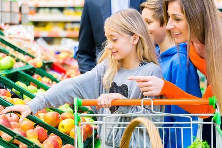Familie im Supermarkt die Auswahl Fr�chte, w�hrend Lebensmitteleinkauf