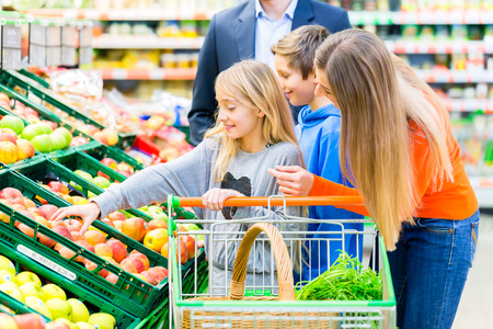 grocery cart: Family in supermarket selecting fruits while grocery shopping