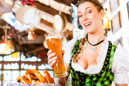 Bavarian woman wearing dirndl drinking wheat beer in German restaurant photo