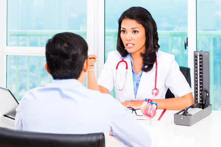 check up: Asian female doctor giving patient medical advice in practice or office Stock Photo