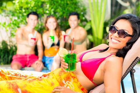personas festejando: Amigos asiáticos de fiesta y bebiendo cócteles de lujo en el hotel o en la piscina del club del partido