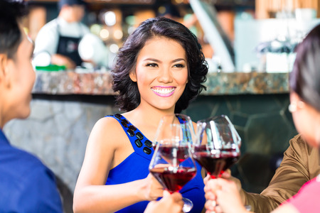 Asian Friends toasting with wine in restaurant photo