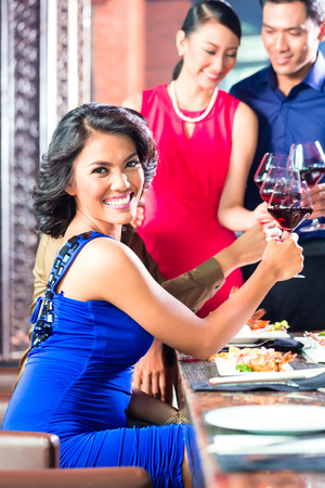 Portrait of Asian friends celebrating with red wine in restaurant photo