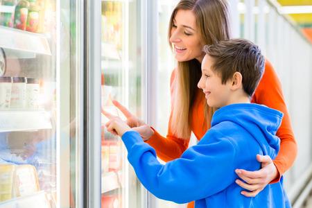 tiendas de comida: Familia seleccionando productos congelados mientras realizan sus compras en el supermercado