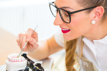 Female dental technician or orthodontist  producing denture with imprint