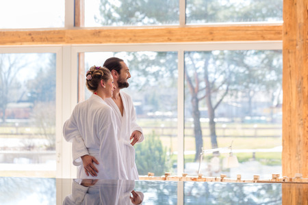 Couple on pool looking relaxed throw window of wellness spa wearing bath robe photo