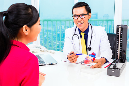 doctor consultation: Asian doctor giving patient medical advice in practice or office Stock Photo
