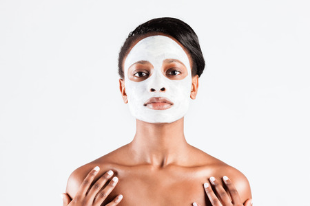 mud woman: Young African woman in Studio doing body care with refreshing facial mask for young and beautiful skin and relaxation